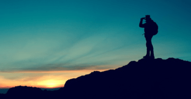 Hunter with binoculars and snake boots at sunset on hilltop