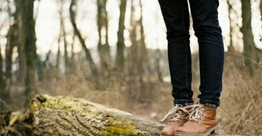 Woman standing on a log with snake boots
