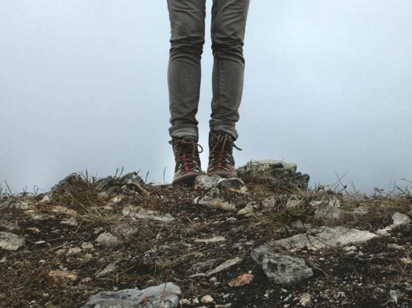 Woman wearing snake boots on rocky summit