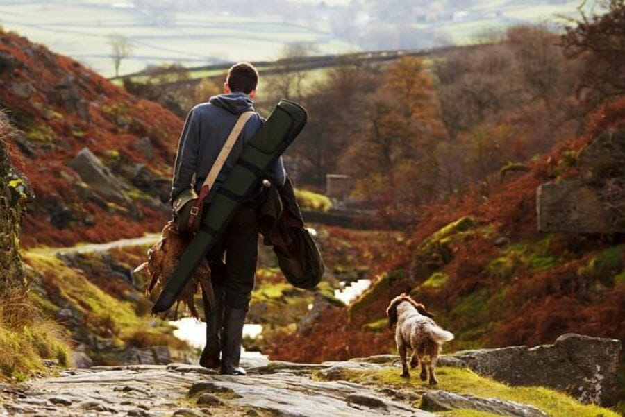 """Man and dog returning from hunting with man wearing 16"""" snake boots"""