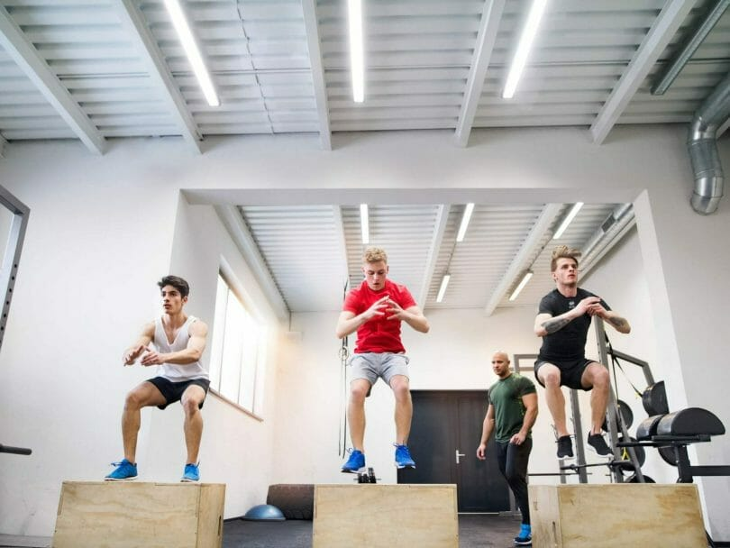 Three guys with a coach doing box jump WOD in CrossFit gym..