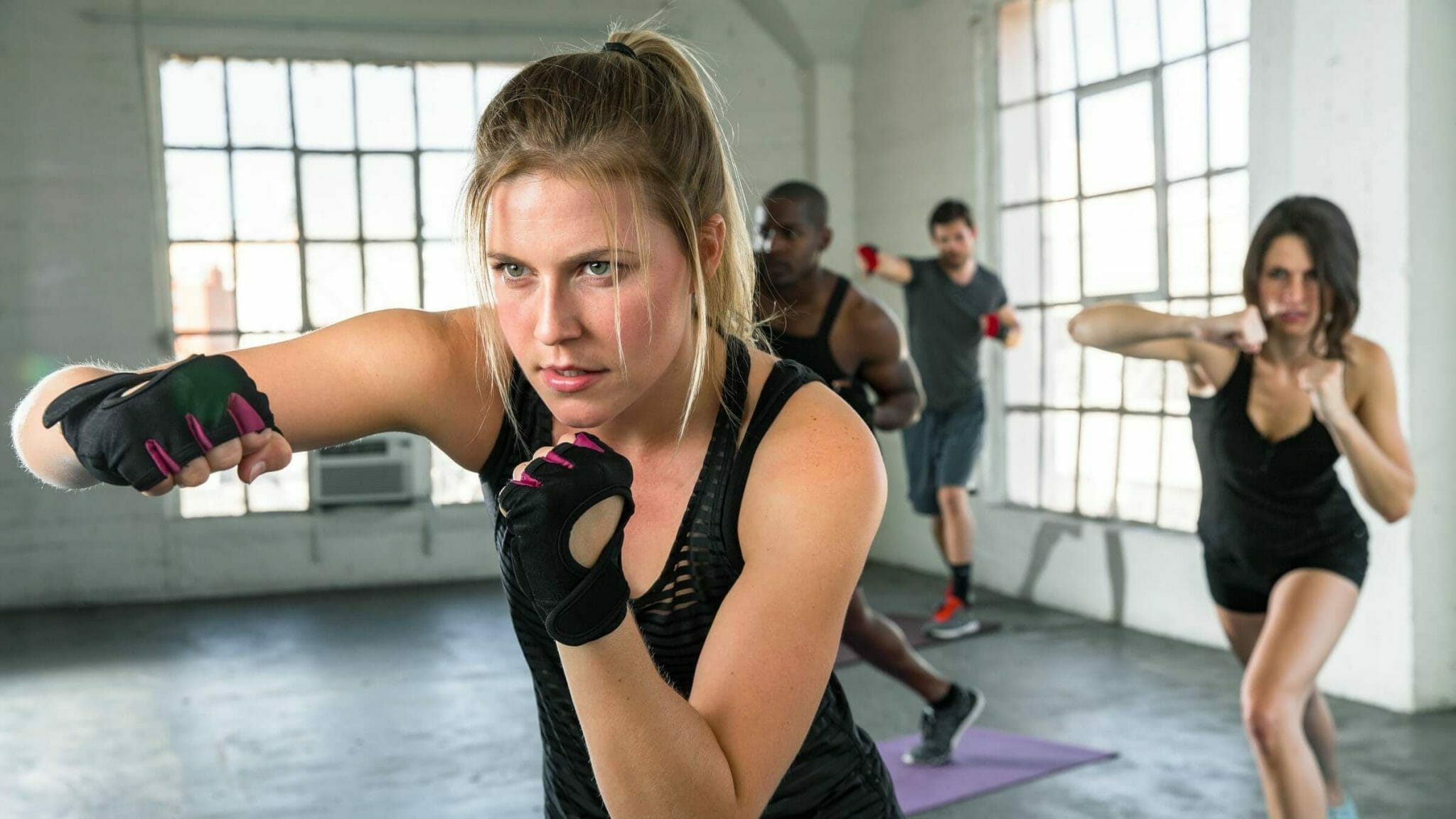 Fitness class in warehouse loft doing air punch drills