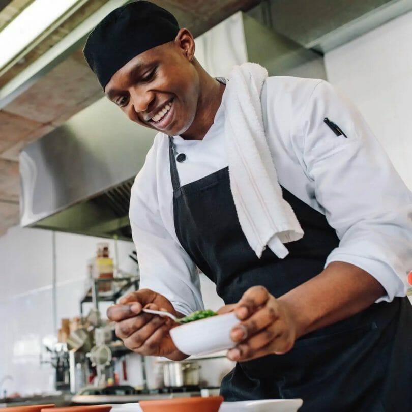 Chef in a black skull cap adding garnish to a dish