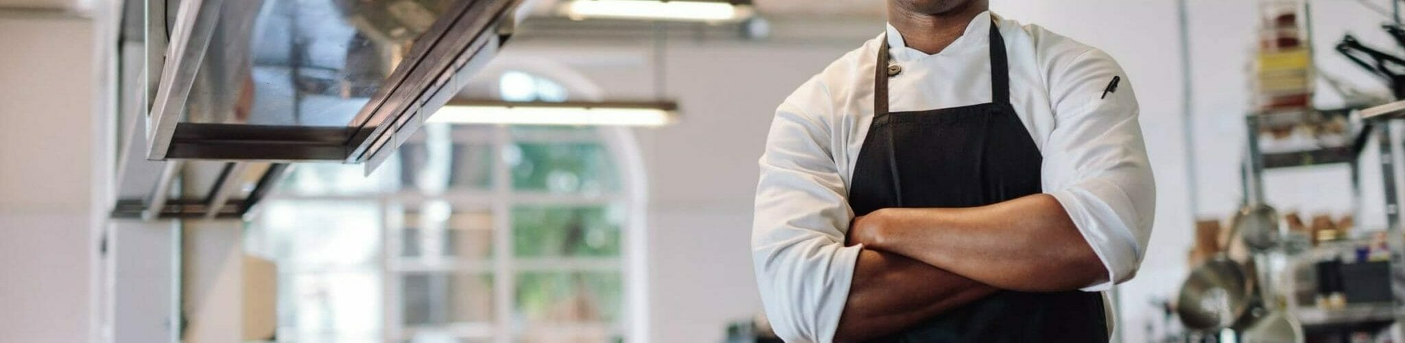 Chef in his kitchen with crossed arms and smiling