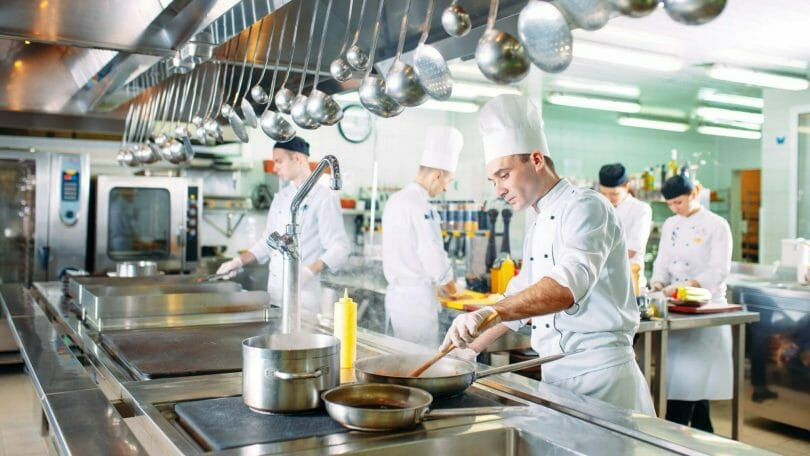 Commercial kitchen with multiple people cooking