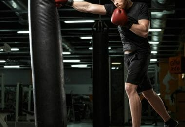 Man in black with black boxing shoes training on heavy bag