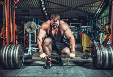 Lifter with weightlifting shoes preparing to perform Olympic lifts with heavy weights.