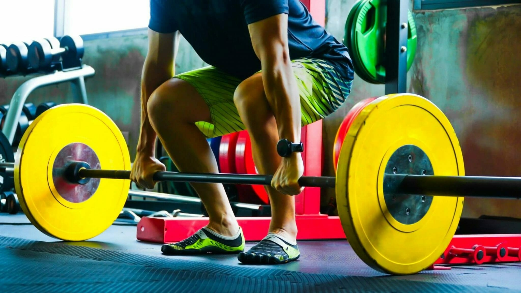 Powerlifter in minimalist squat shoes with yellow weights in gym.