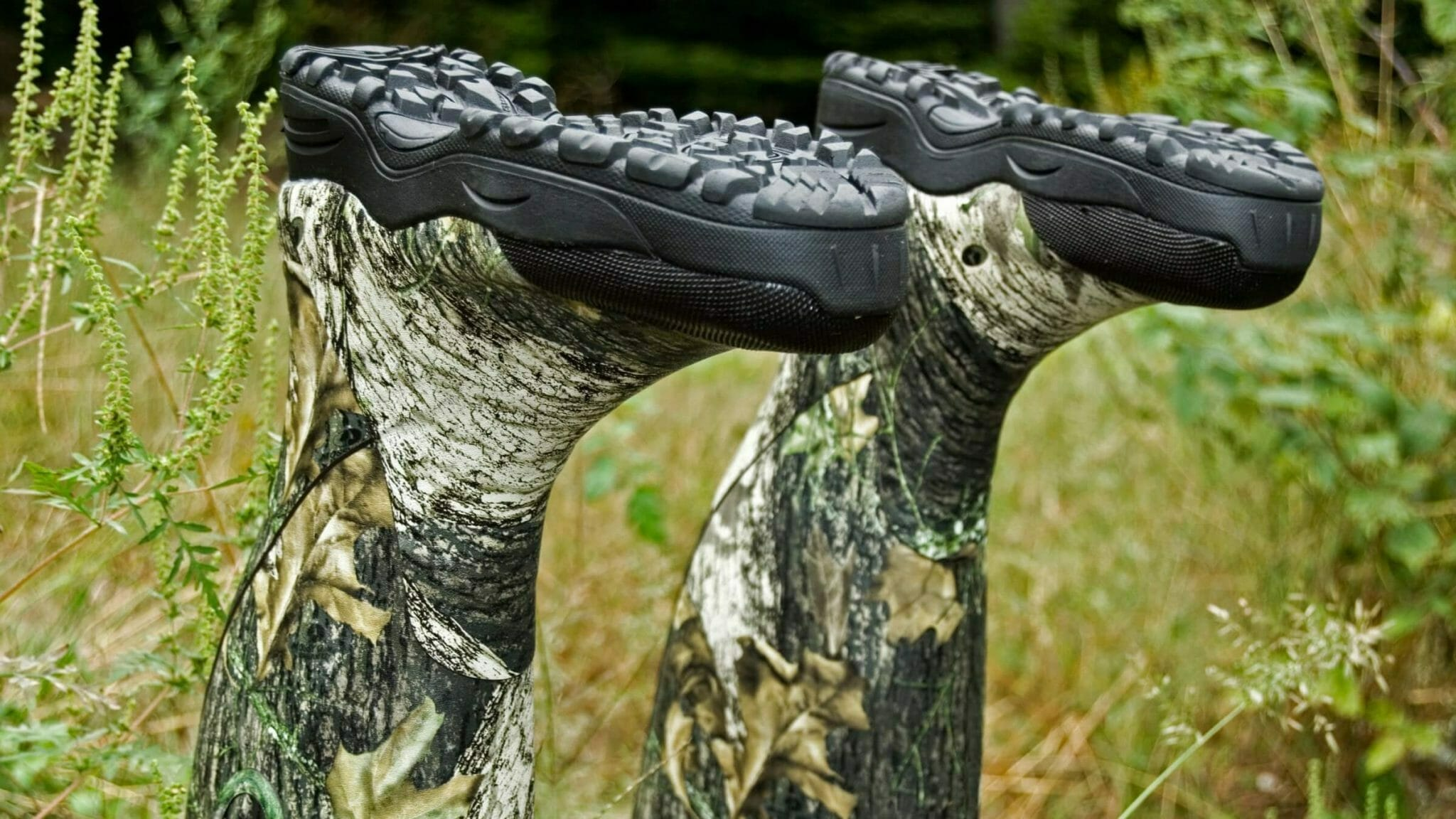 Pair of muck boots snake proof boot sticking up from the grass. Design of the outsole and midsole featured.