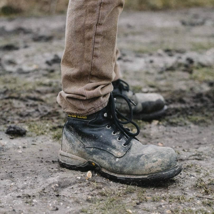 Person standing in muddy black hiking boots with oversized laces on a mud trail with sparse blades of grass.
