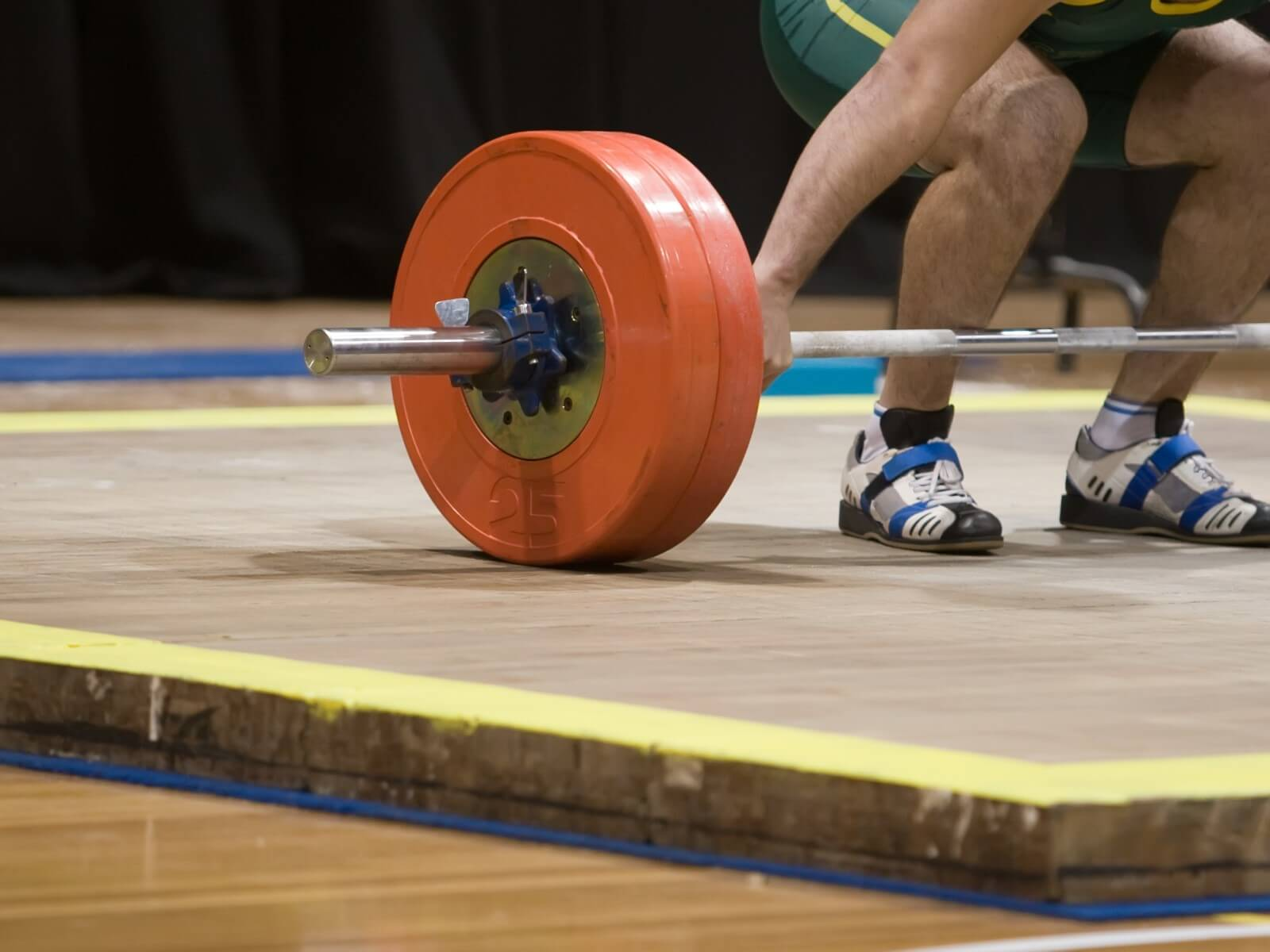Olympic weight lifter wearing adidas adistar shoes preparing for clean and jerk.