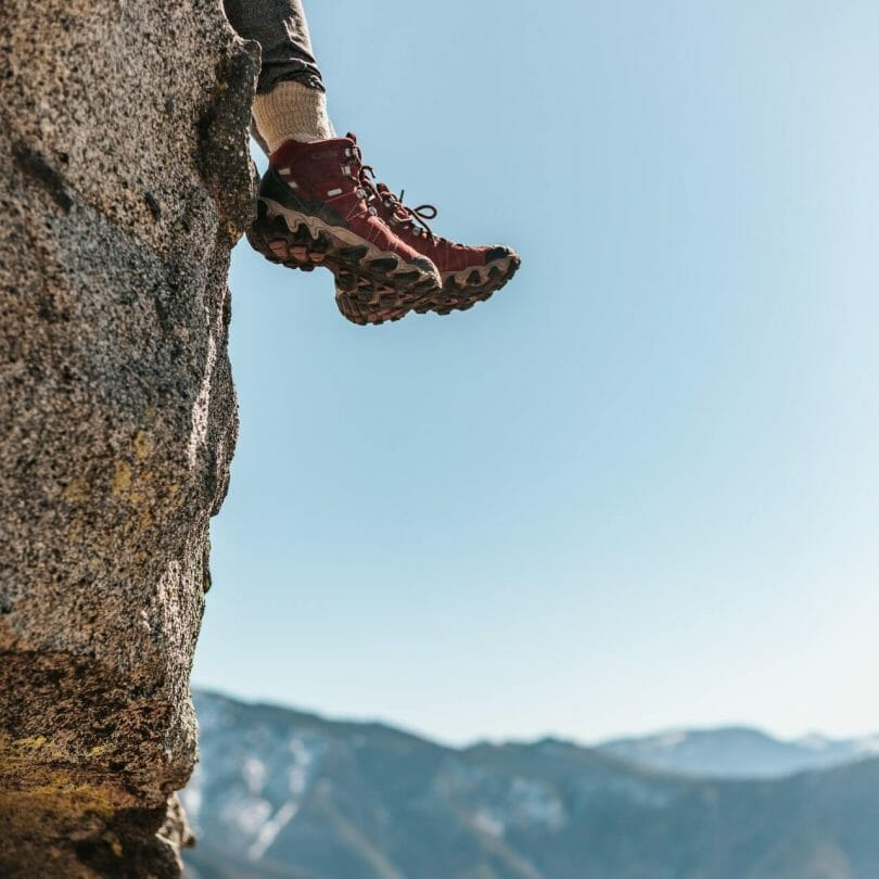 Person sitting on a ledge with feet dangling in front of mountain background.