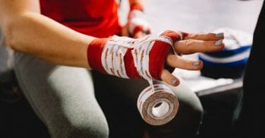 Close up of woman getting wrist wrapped with tape after failure to prevent wrestling injury.