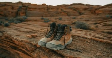 Pair of hiking boots with rubberized toe and reinforced gusseted tongue sitting on red rocks in the desert.