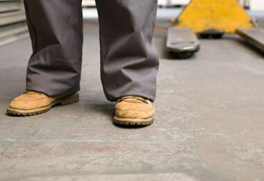 Tan safety boots in front of a skid at a warehouse with concrete floors