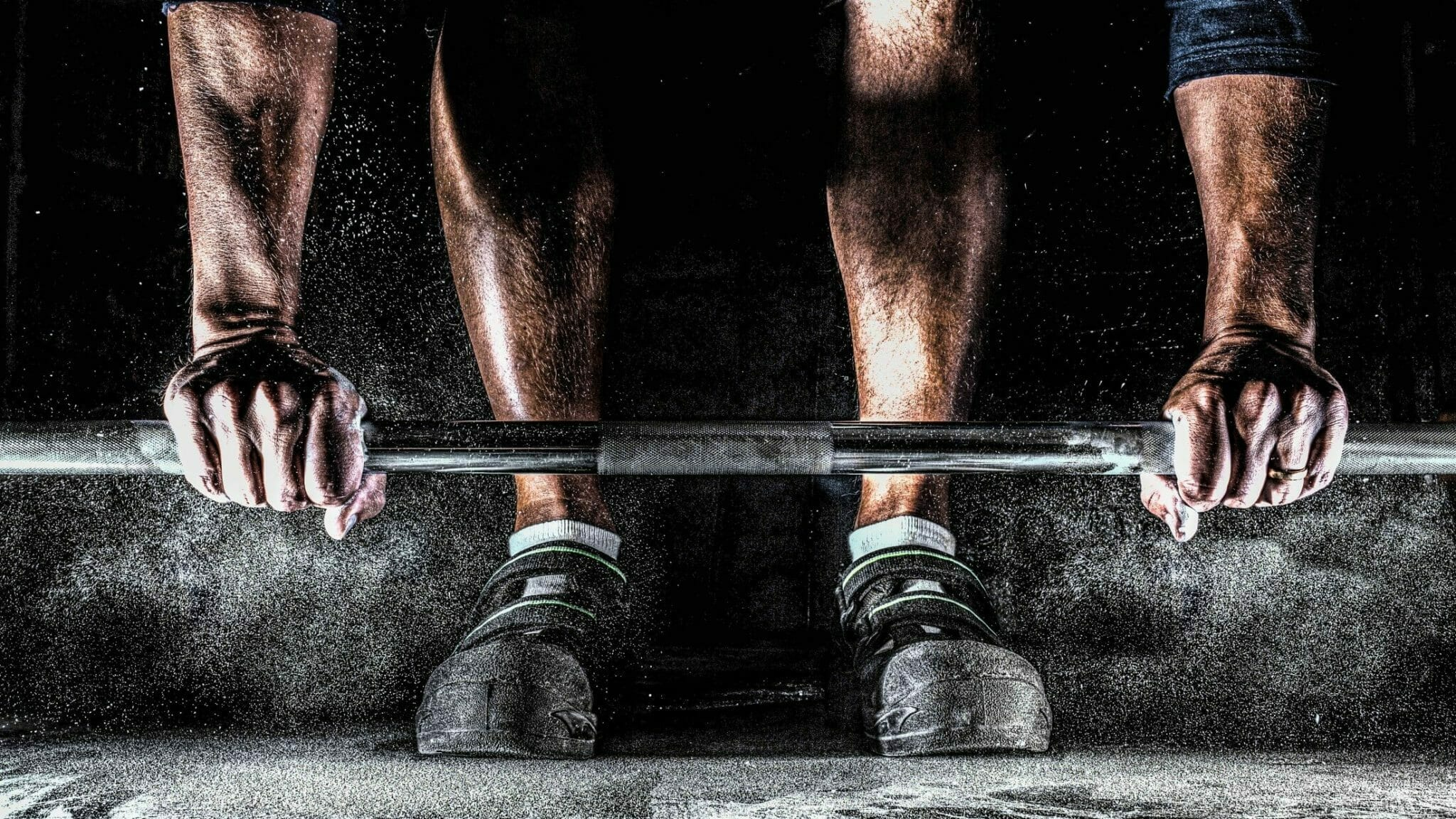 Heavy chalk in the air as man in high heel raise lifting shoes prepares for deadlift.