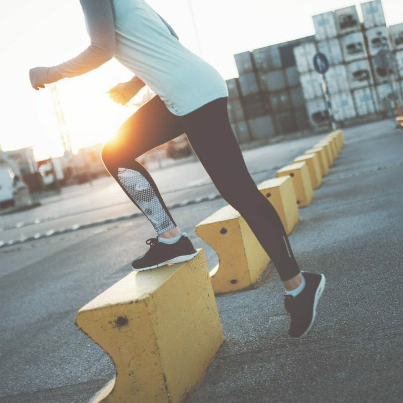 Woman at sunrise doing step workout.
