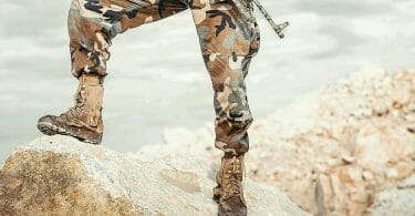 Person standing on rock in tactical boots with rifle and camouflage pants.