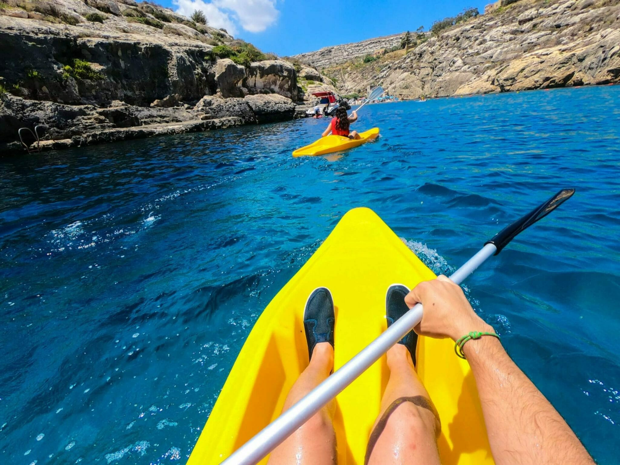 Two kayakers in bright yellow kayaks with fast moving in canyon on a sunny day
