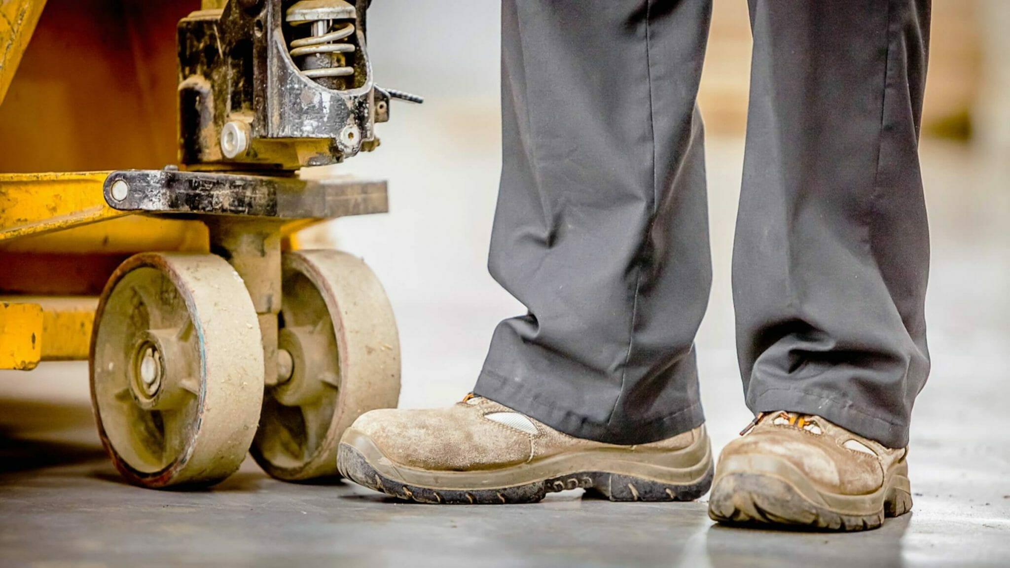 Worker with composite toe safety boots in warehouse with heavy equipment