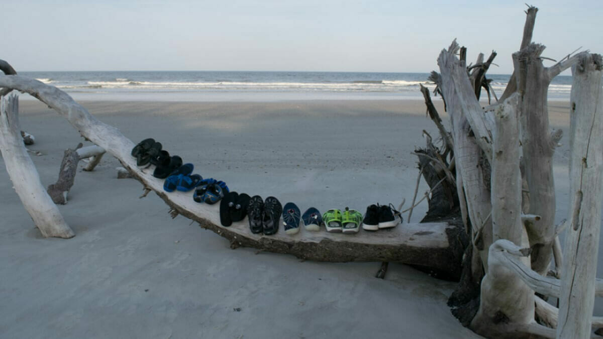 Some of the water shoes we tested lined up on a log on the beach with the ocean in the background