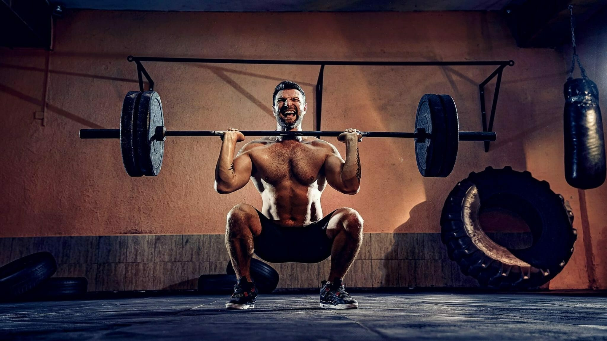 Man in squat with weights in middle of lifting while using incorrect powerlifting shoes.