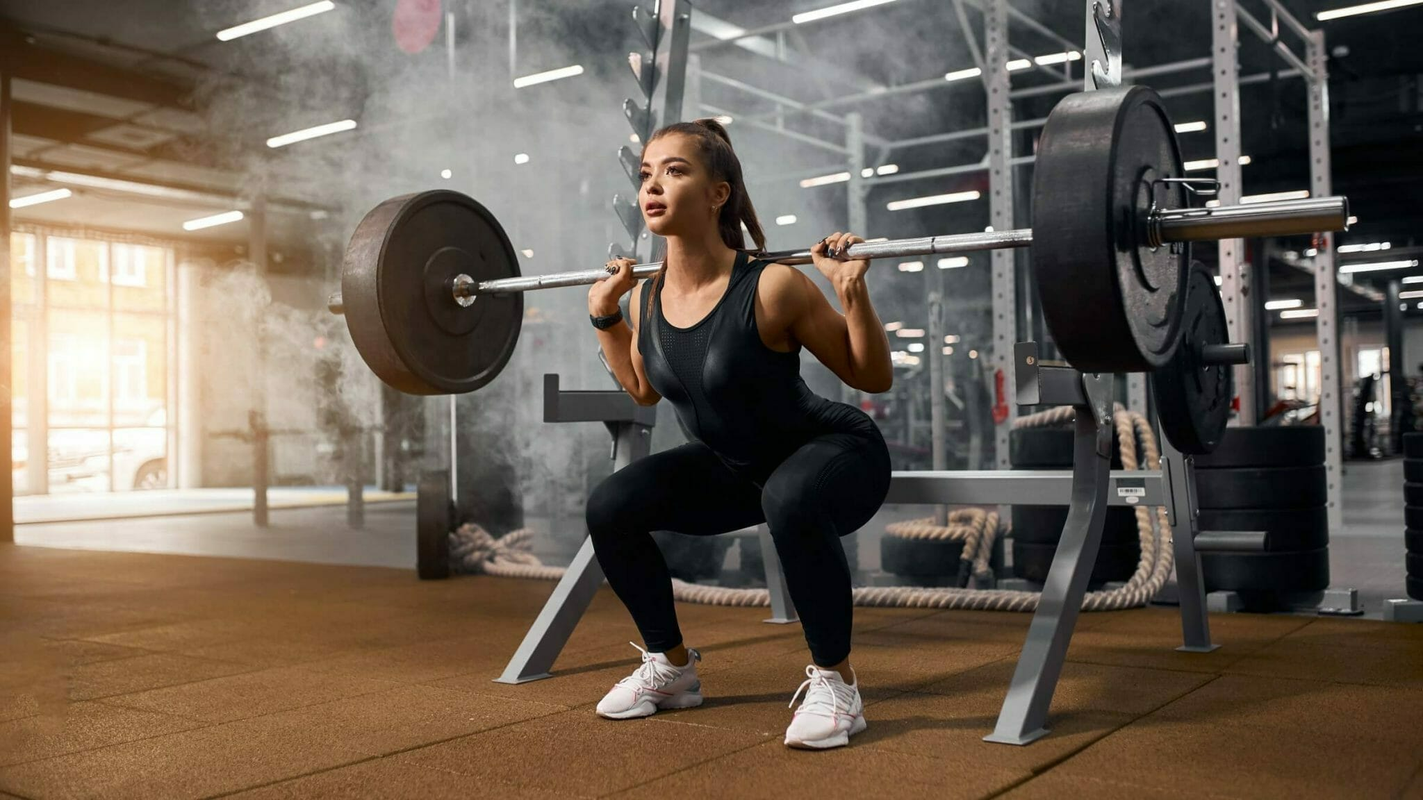 Doing squats with white women's weightlifting shoes and black spandex gear.