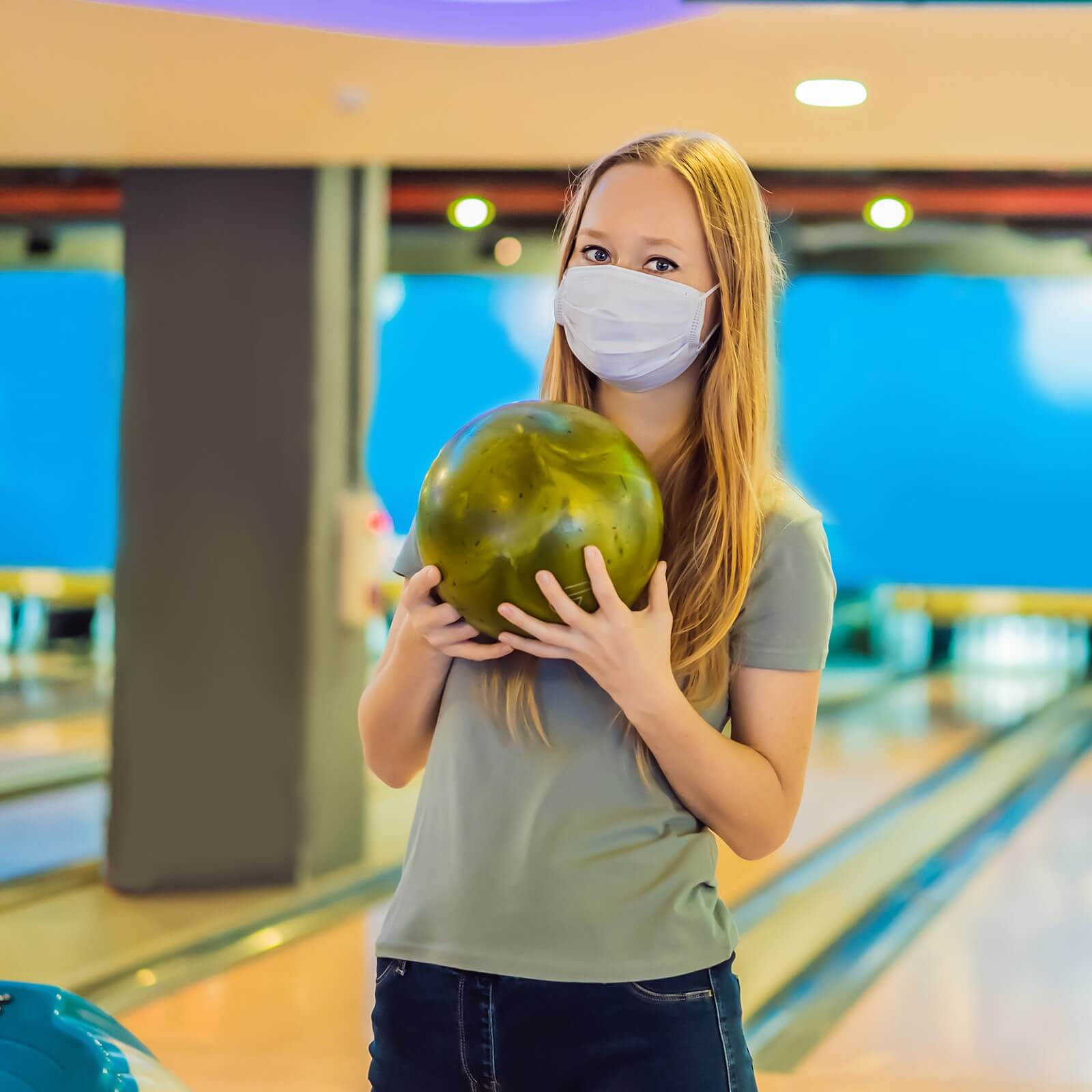 Woman in mask holding bowling ball during the pandemic