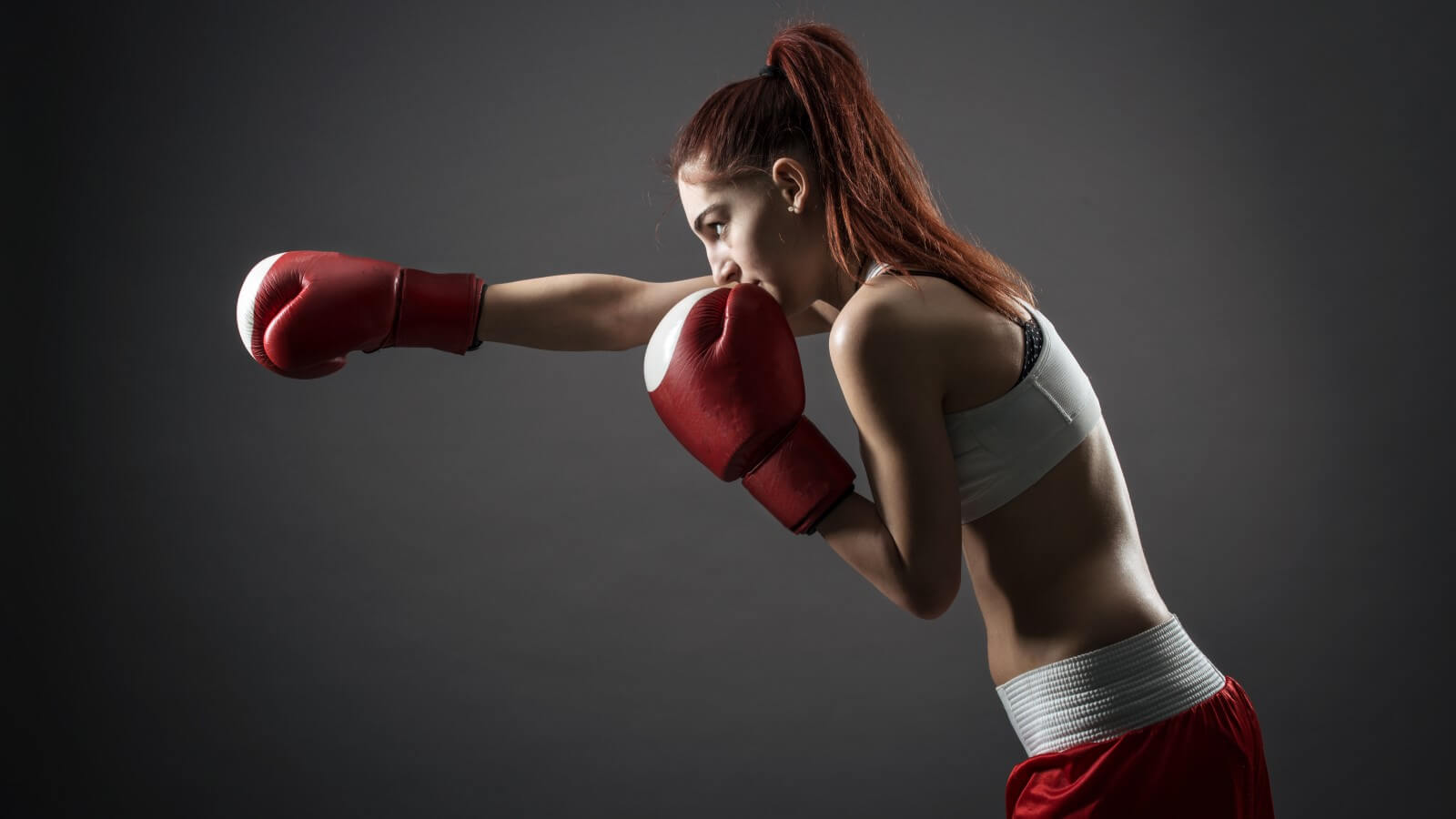 Woman practicing right jab in red boxing gloves