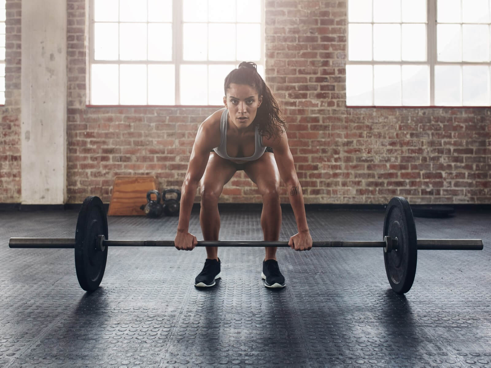 Woman with pony tail preparing for lift in women's weightlifting shoes.