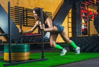 Woman pushing sled with 100kg weights using some of the best CrossFit shoes for traction.
