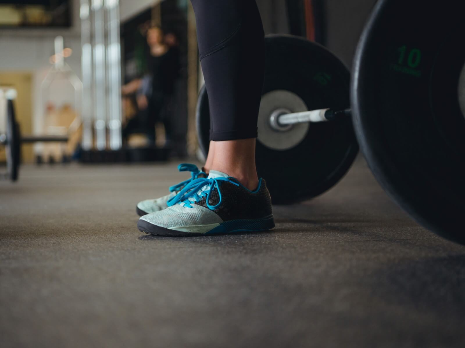 Woman standing in front of barbell wearing teal and black women's weightlifting shoes in gym.