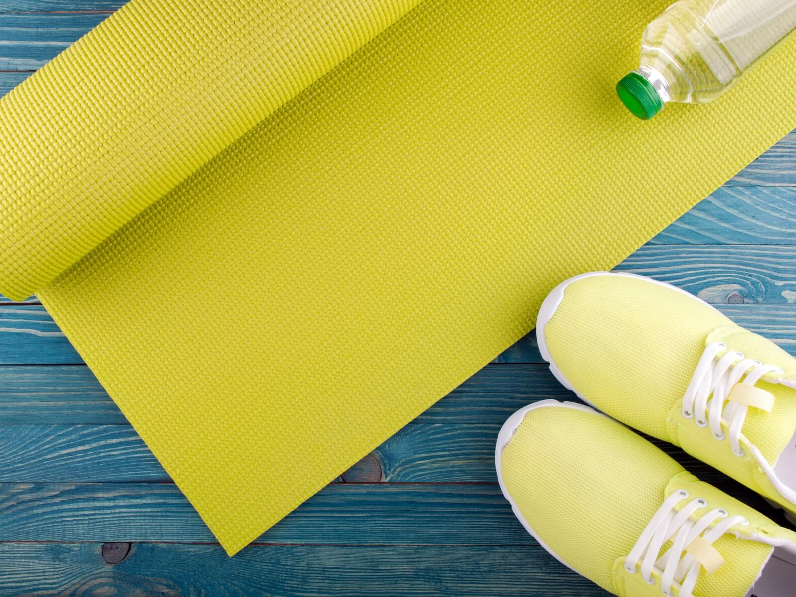 Yellow mat and shoes with water bottle.
