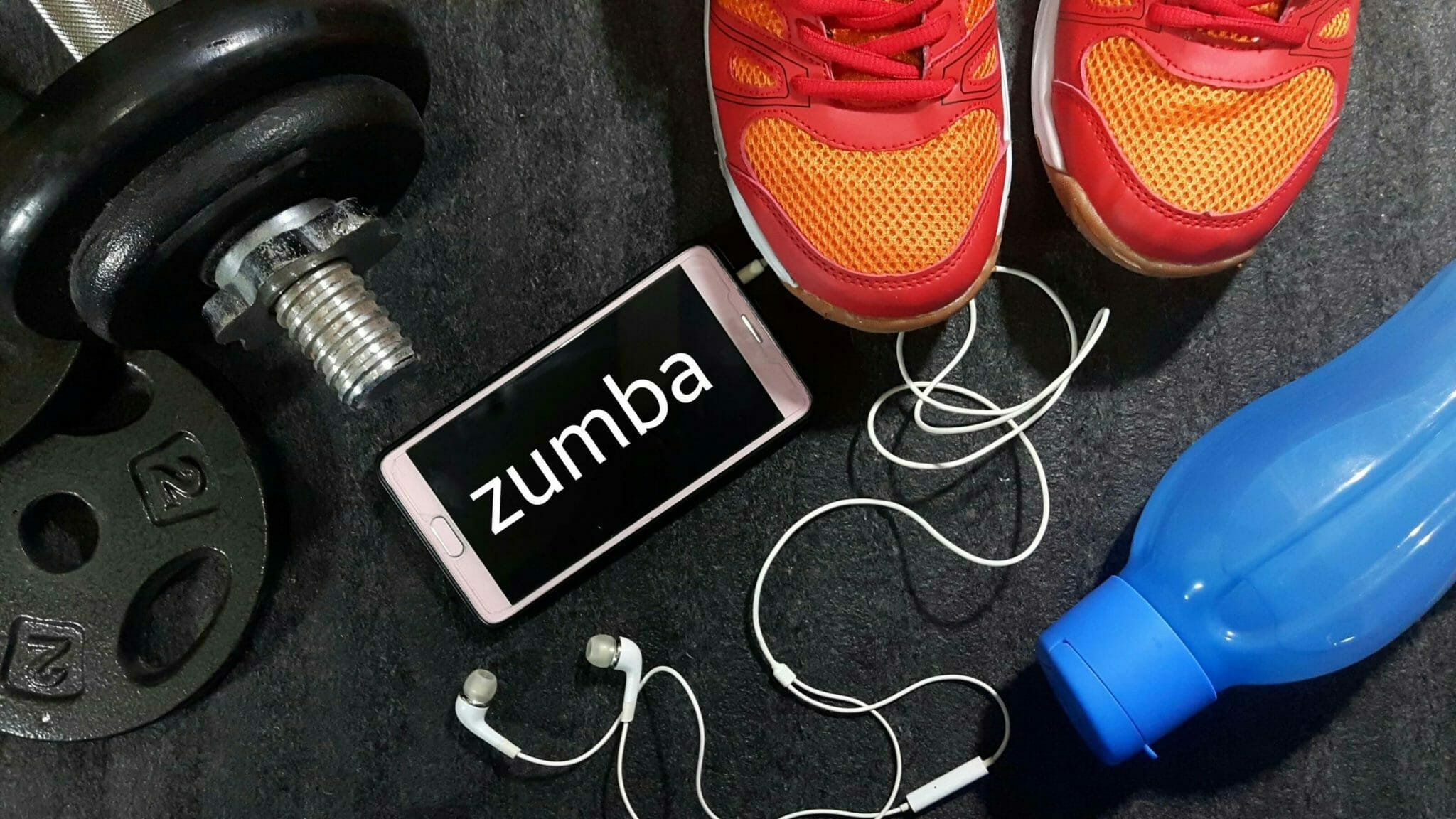 Zumba shoes featured with blue water bottle and iPhone and dumbbell